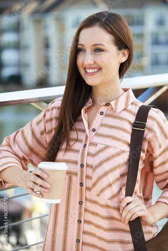 Young Woman With Takeaway Coffee Walking To Work In Urban Setting