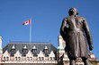 Statue of Captain James Cook and the canadian flag flying in Victoria, British Columbia, Canada
