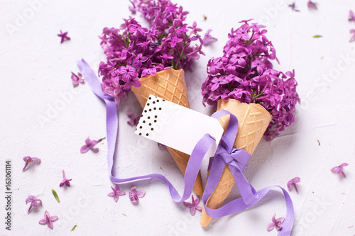 Fresh lilac flowers in waffle cones with ribbon and empty tag
