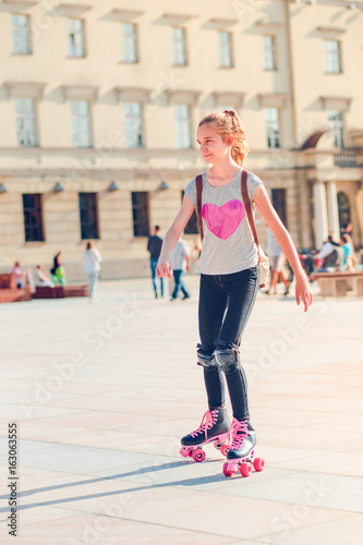 Young girl roller skating in a town