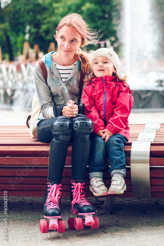 Sisters sitting on bench in a town