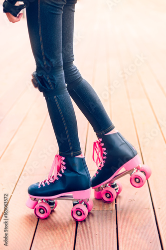 Legs of young roller skater standing on wooden stage