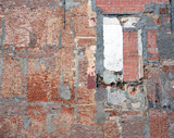 part of old derelict brick wall with several different bricks and cement patches