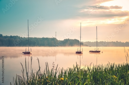 Spring morning waterfront landscape. Boats on the foggy lake.