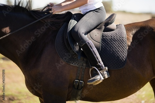 Child riding a horse in the ranch