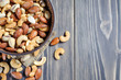 Mixed nuts spilling out of bowl on wooden table. Macro still-life with shallow dof