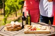 Midsection of friends by food and wine bottles on table