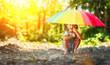 Leinwandbild Motiv Happy child girl laughs and plays under summer rain with an umbrella
