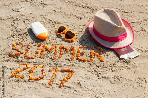Inscription summer 2017, accessories for sunbathing and passport with currencies dollar at beach