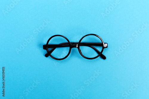 A pair of round glasses on a bright blue background