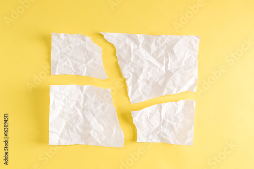 Torn pieces of paper on a yellow background