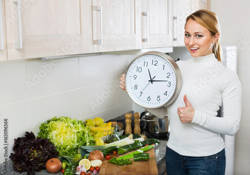 Portrait of happy  woman holding clocks