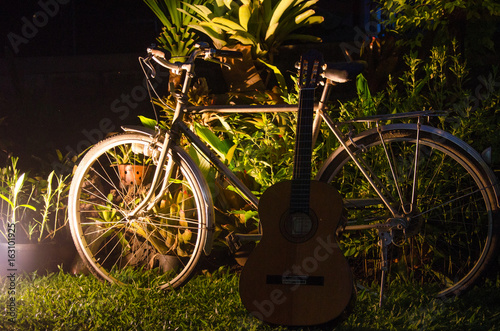 Old Ancient Bike Park in the lawn and have a leaning guitar. Beautiful night atmosphere