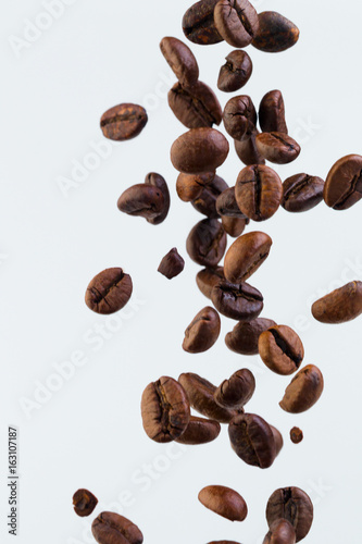 Staande foto Koffiebonen Falling grains of roasted coffee on a white background