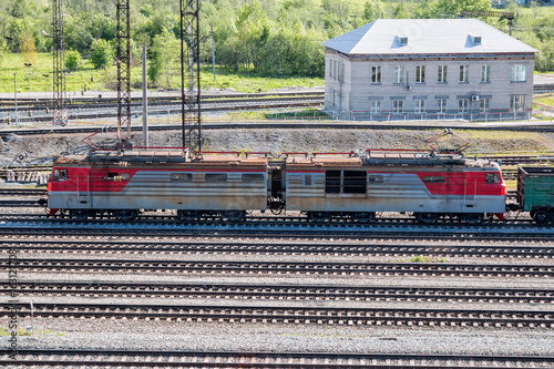 Electric locomotive with freight carriages passes through the railway station in the village