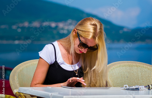 Close-up girl uses a tablet to communicate in social networks on a vacation on the beach.