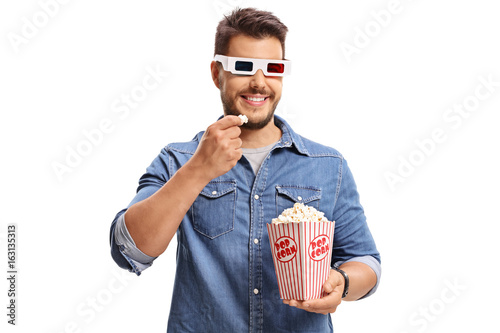Man wearing a pair of 3D glasses and eating popcorn
