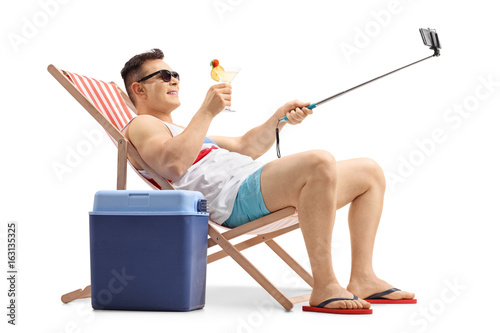 Young man with a cocktail taking a selfie