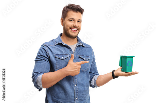 Young man holding a small recycling bin and pointing