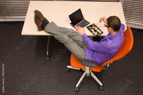 caucasian man with legs on the desk, eating sushi with chopsticks