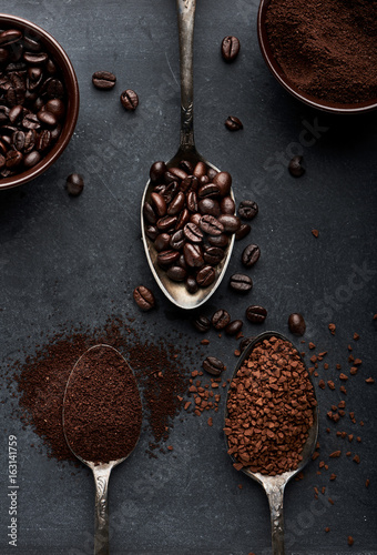 Three kinds of coffee in spoons and cups over dark background.
