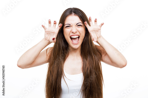 Beautiful young woman shouting and growling like an animal over white background Poster