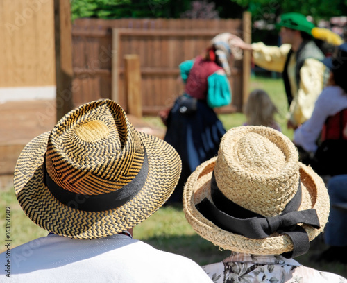 Rear view of couple wearing straw hats watching outdoor play.