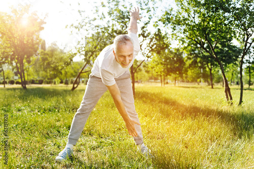 Cheerful delighted aged man enjoying sport exercises