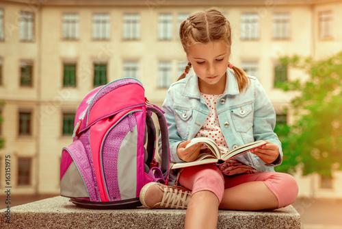 Fototapeta kind liest vor der schule