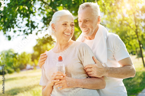 Cheerful loving aged couple resting in the park