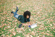 Young black woman lying on autumn leaves typing on her convertible laptop. Fall season leisure with tablet outside at the park.
