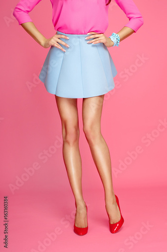 Female legs with red heels and short blue skirt