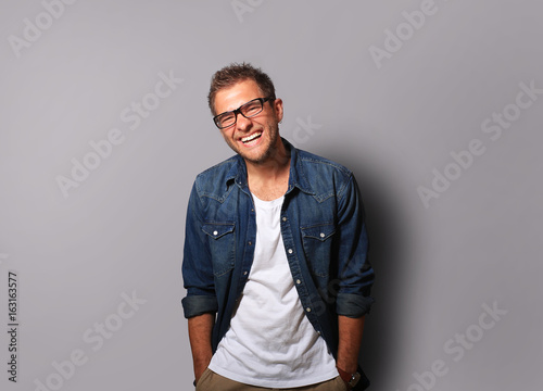 Young man in a denim shirt is smiling