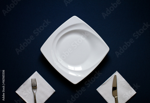 White plate, knife and fork on dark blue table. Top view.