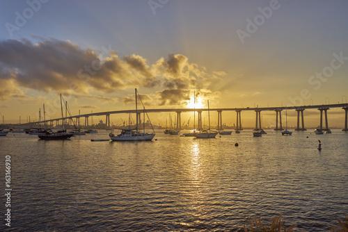 boats under and beautiful sunrise over the Coronado Bridge, San Diego California