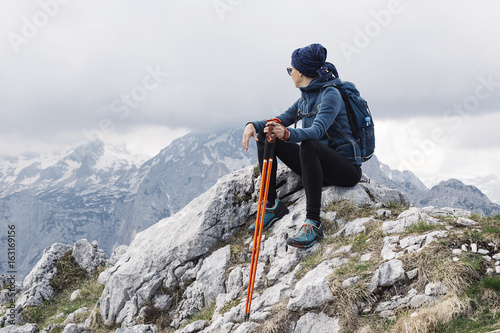 Female hiker enjoying the mountain air sitting on a hill and resting