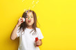 Beautiful little girl blowing soap bubbles on yellow background