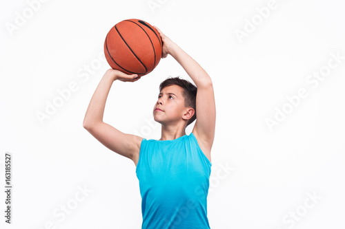 Fotobehang Basketbal Young boy playing basketball isolated on white