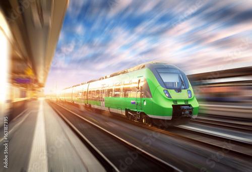 Wysoki prędkość pociąg w ruchu przy stacją kolejową przy zmierzchem w Europa. Piękny zielony nowoczesny pociąg na peronie kolejowym z efekt rozmycia ruchu. Przemysłowa scena z pociągiem pasażerskim na linii kolejowej