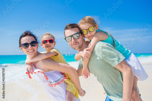 Happy beautiful family of four on a tropical beach. Parents and kids background seashore on beach vacation