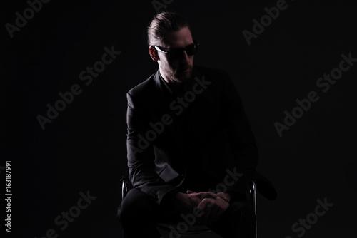 Poster Mann in schwarzem Anzug vor schwarzem Hintergrund