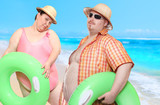 Obese couple in swimsuit with green lifebuoy. Holidays on the beach.Funny people sending greeting from tropical paradise. - 163189906