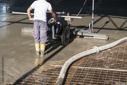Pracownik budowlany z maszyna do wyrównywania laserem wyrówniarki betonu