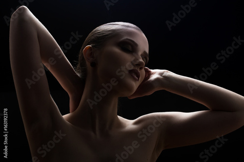 Black and white shot of woman posing sensually with closed eyes on black background