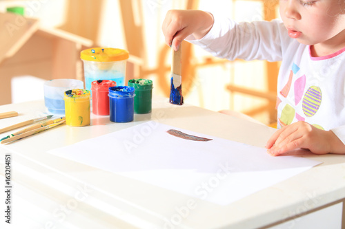 Child draws with brush in paint