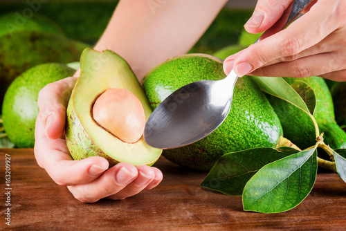 Hands of woman holding spoon and half of avocado
