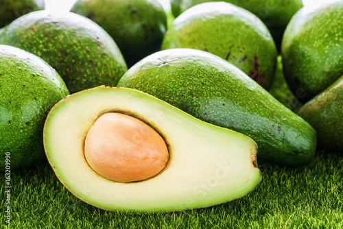 Closeup view of fresh ripe avocados on green grass