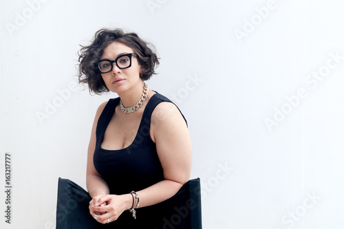 Portrait of young plus size model with dark curvy hair wearing fashionable black glasses and looking at camera. Composition with copy space