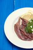 anchovies with lemon on white plate - 163222386