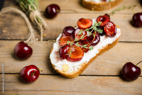 Bread with ricotta cheese and cherries on the wooden background. Shallow depth of field.